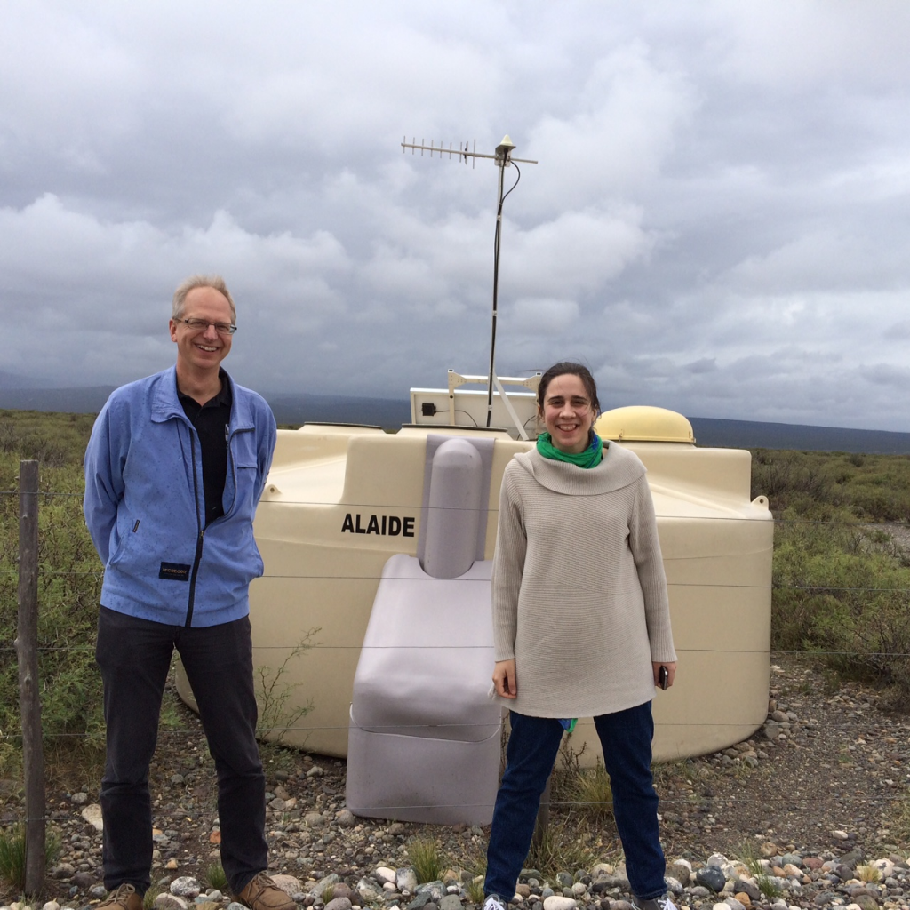 "Two Auger Collaborators posing with ""Alaide"", one of the 1660 surface stations of the Pierre Auger Observatory"